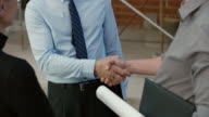 Investor shaking hands with two architects outside at the construction site