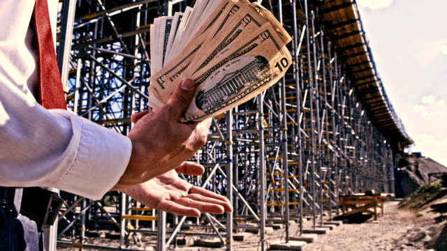SLO MO Investor with money at the construction site