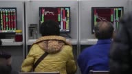 Investors watch the stock monitors and play poker on the stock trading floor on December 9 2014 in Beijing China