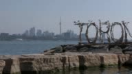 Prince Harry arrives in Toronto EXT PAN wide shot bay with CN Tower and 'Toronto' sign