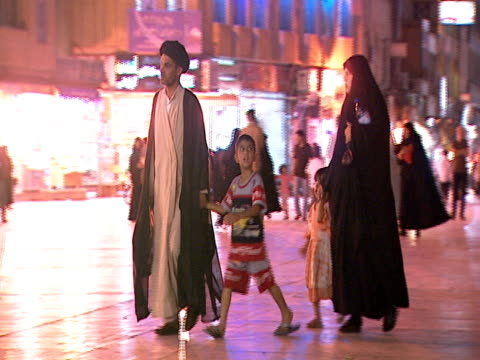 PAN Iranian family walking at night in a plaza / Qom Iran