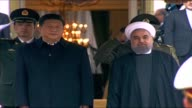 Iranian President Hassan Rowhnai welcomes his Chinese counterpart Xi Jinping during a welcoming ceremony at the presidential palace in Tehran Iran on...