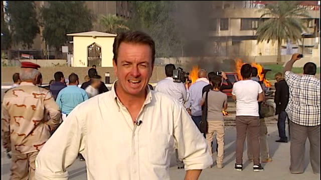 Report on what has changed since the war IRAQ Baghdad EXT Actors firing guns towards lorry on film set SOT Back view production staff speaking with...