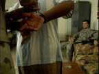 Iraqi Army officer handcuffing suspect and making him sit down while US soldiers watch interrogation / Mahmudiyah Iraq / AUDIO