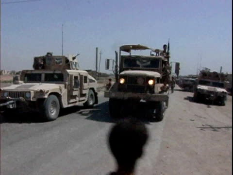 Iraqi army truck driving down road with US military vehicles in background / Mahmudiyah Iraq / AUDIO