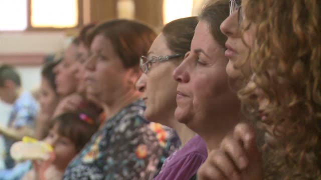 Iraqi Christians who fled the violence in the village of Qaraqush about 30 kilometres east of the northern province of Nineveh attend a mass at the...