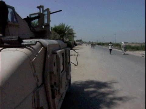 Iraqi civilians walking down road near US Army armored vehicle / Mahmudiyah Iraq / AUDIO
