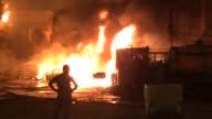 Iraqi firefighters try to extinguish fire following a car bomb blast in Baghdad Iraq on June 9 2015 A Car bomb went off near restaurants and shop in...
