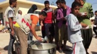 Iraqi men are given food in Debaga refugee camp where newly arrived refugees from Mosul have sought shelter as the ongoing offensive to retake Mosul...
