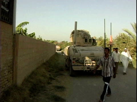 Iraqi men walking past US armored vehicle on their way to sign up for Concerned Local Citizens volunteer program / Haswa Iraq / AUDIO