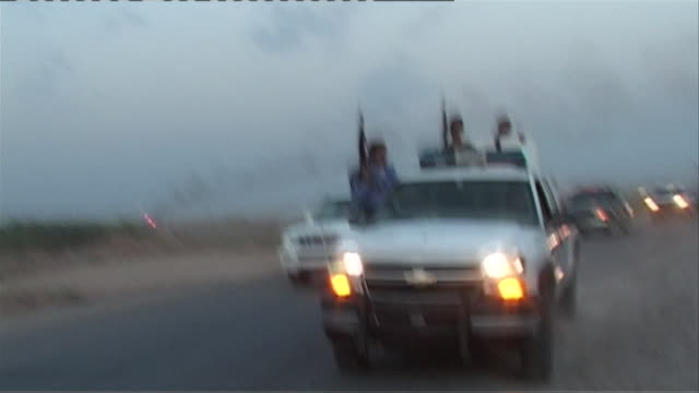 MS REAR POV SHAKY Iraqi patrol vehicle filled with armed officers speeding ahead of convoy, Haditha, Al Anbar, Iraq