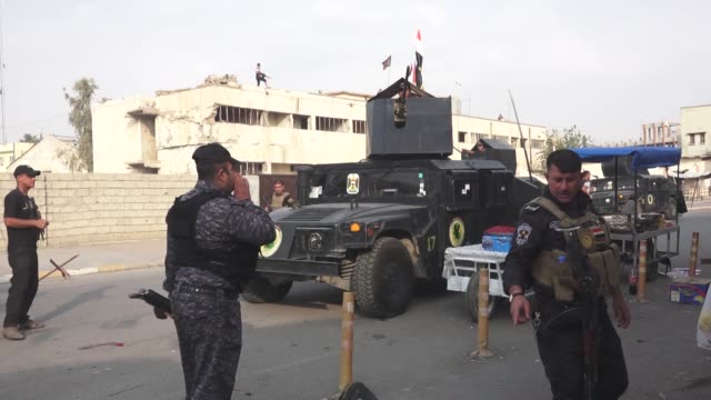 Iraqi security forces inspect the site of a twin suicide attack near a Shia shrine on Atlas street in central Kirkuk Iraq on November 05 2017 At...