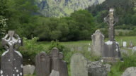 Ireland Glendalough cemetery and high cross in mountains pan and zoom