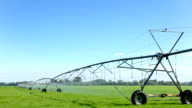 irrigation machine on meadow in blue sky