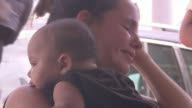 Islands struck by Hurricane Irma struggle to recover as response of UK criticised People with suitcases outside airport Young child Child asleep...