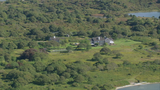 AERIAL Isolated hamlet on island with shorelines in front and beyond / Aquinnah, Massachusetts, United States