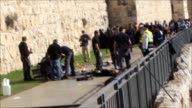 Israeli officials work at the crime scene after an alleged Palestinian stabbing attacker wounding three Israelis was shot dead Israeli security...