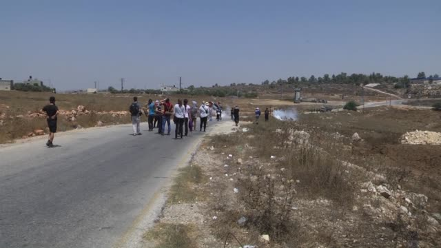 Israeli security forces fire tear gas canister as a group of Palestinians protest the construction of Jewish housing units and the separation wall in...
