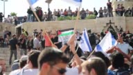 Israelis wave national flags to commemorate Jerusalem Day on May 24 2017 as peace activists and Palestinians stage a demonstration at the Damascus...