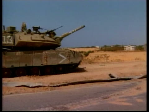 Isreal attacks Gaza strip Isreal attacks Gaza strip ITN Israeli tank as gun turret swivelling round PULL OUT GV Israeli armoured vehicle along road...