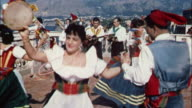 Italian couples dance their traditional dances with musicians in the background on the Amalfi Coast in Italy.