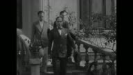 Italian legation building Italian envoys walking down steps Heir Presumptive Tati getting out of walking away from convertible car