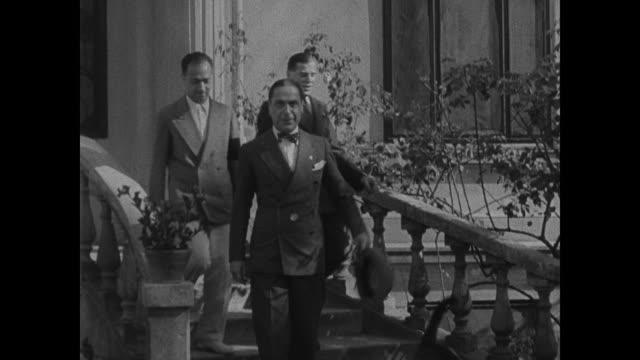 Italian legation building Italian envoys walking down steps Heir Presumptive Tati getting out of walking away from convertible car