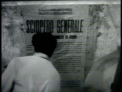 Italian male and female putting poster onto wall 'general strike' WS Large crowd of people gathered outside building Italian soldiers in Jeep labeled...