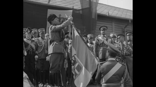 Italian troops marching away from camera / VS Benito Mussolini places ribbon at top of flag staff and decorates man and woman in black veil whose...