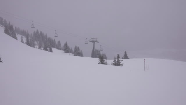 It´s foggy and it´s snowing  in the mountain. Empty chairlift in functioning at the bottom.
