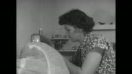 VS Iva Sprout wife of USAAF veteran Dale Sprout works at sewing machine in room of their homestead house she sews a dress / VS Iva looks at the...