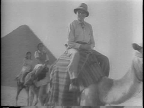 Jack Benny walking in Cairo and buying something from a boy / Benny on a camel with others / Benny riding a camel near the Pyramids / various angles...