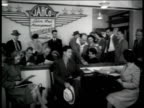 Jack Heintz employment office office crowded w/ applicants Male filling out paperwork Women working in office filing CU Overseas IN Out boxes