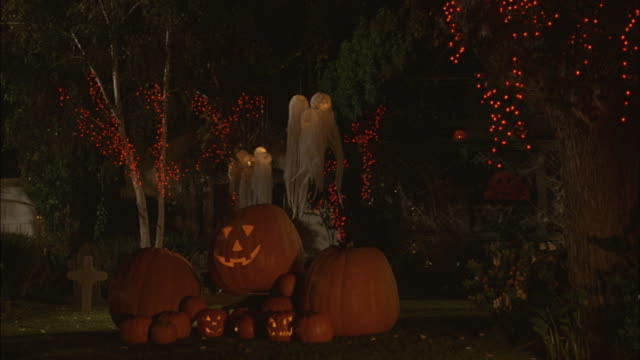 Jack-o-lanterns and lights decorate the yard of neighborhood home.
