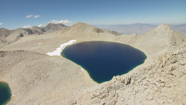 WS AERIAL POV Jagged ridgeline revealing large alpine lake with Sierra Nevada and Owens Valley in background / California, United States