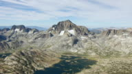 WS AERIAL POV Jagged rocky mountain range including Mount Ritter and Banner Peak with ThoUnited Statesnd Island Lake in Yosemite National Park / California, United States