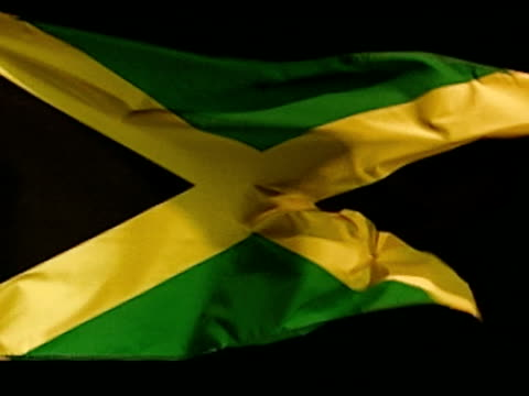Jamaica country flag flying against black BG Diagonal yellow cross divides flag into four triangles green black