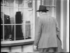 James Cagney calls Edward Arnold away from a shop window to have a conversation / high angle shot of Americans working in munitions factory / medium...