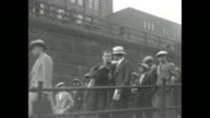 CU James Joseph Tunney on train / MS Tunney walks down ramp with man and is followed by other men and boys / CU Tunney and manager Billy Gibson / row...