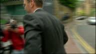 James Murdoch resigns as Chairman of BSkyB Wapping EXT James Murdoch along towards News International headqaurters building past security guard