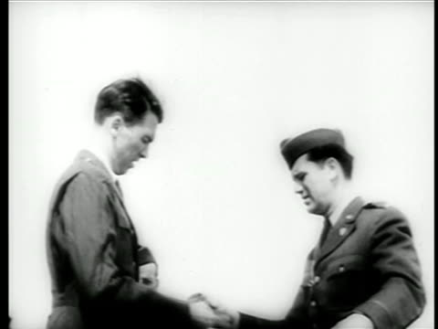 James Stewart putting on Air Force uniform as officer looks on / WW II / documentary