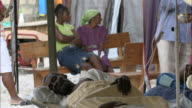 January 4 2011 MONTAGE Patient resting in cot while other villagers are sitting on a bench inside a medical tent / Mirebalais Haiti