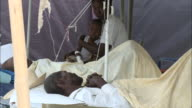 January 4 2011 MONTAGE Patients laying in beds mother holding her child on her lap in a medical tent / Mirebalais Haiti