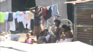 January 6 2011 MS Mother and children hanging outside of makeshift home with cloths hanging on line beyond / Haiti