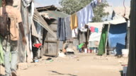 January 6 2011 HA Residents walking through residential slums beyond hanging laundry / Haiti