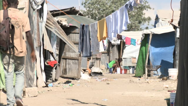 January 6 2011 HA Residents walking through residential slums beyond hanging laundry / Haiti