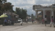 January 6 2011 WS Villagers walking and riding motorcycles in streets / Leogane Haiti