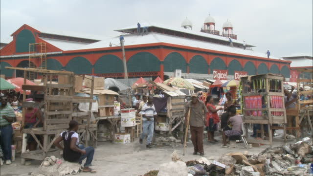 January 7 2011 WS Iron Market under reconstruction towering over adjacent market of makeshift wooden stalls bustling with activity amid heaps of...