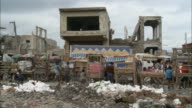 January 7 2011 LA Pedestrian and vehicle traffic passing through outdoor market of makeshift wooden stalls surrounded by heaps of rubble in the...