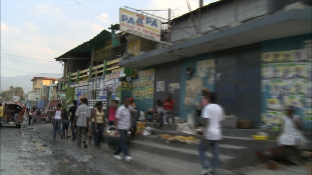 January 8 2011 POV Driving past shopkeepers and merchandise on sidewalk in front of dilapidated buildings on bustling street after 2010 earthquake /...